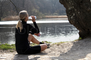 Sporty blond running girl pauses and drink water from a bottle by a lake