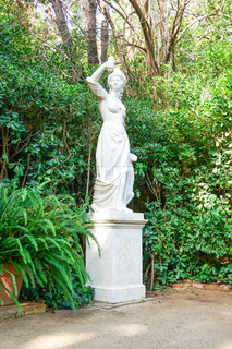 Beautiful statue of young sad woman in the summer park