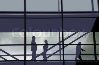 Business people seen as silhouettes through a glass corridor