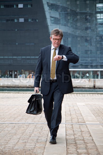 Business man walking and looking at his wristwatch