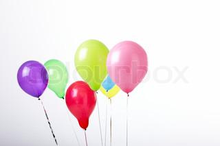 Syv farverige balloner samlet i én klump