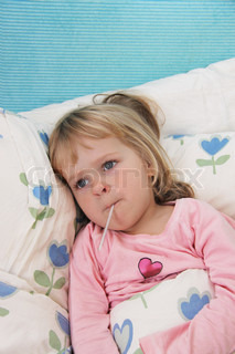 Sick little girl with fever thermometer in bed