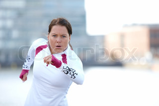 A young brunette caucasian woman in sportswear and running in the harbour