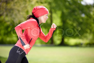 A young brunette caucasian in red sportswear running in the park