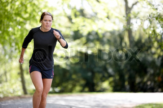 A young brunette caucasian woman  in sportswear and running in the park