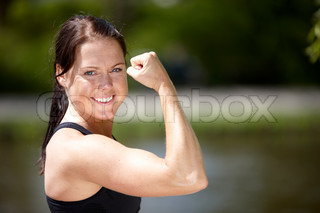 A young  smiling brunette caucasian in sportswear showing her biceps