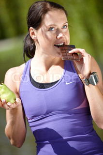 A young brunette female in violet sportswear holding a pear and eating a chocolate bar