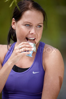 A young  brunette female in violet sportswear eating chocolate energy bar