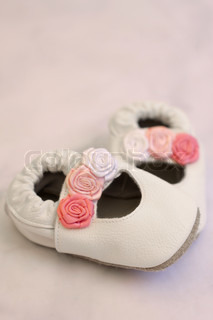 08995800f White leather shoes with roses for a small baby girl. Shot on grey  background, ...