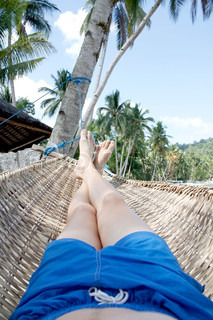 A man with shorts relaxing on a hammock