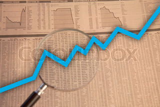 Magnifying glass examine stock market with blue business arrow going up