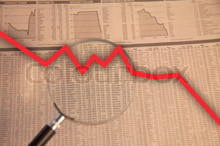 Magnifying glass examine stock market with red business arrow going down