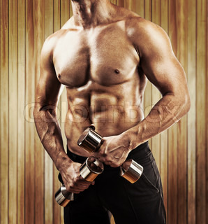 close up view on muscular male torso man holding small glossy dumbbells in hands instagram stile