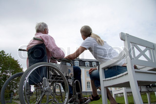 Old man in wheelchair talking with a young blond girl sitting on a garden bench at a nursing home