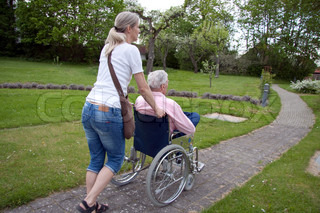 Blond girl running old man in wheelchair at a nursing home