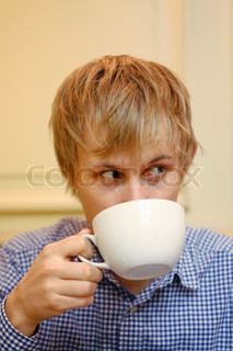 A man drinking a big cup of coffee