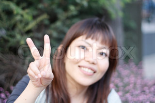 An Asian woman gesturing a peace sign