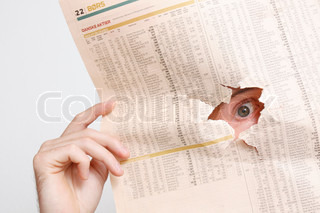 A businessman looking at a hole from a newspaper