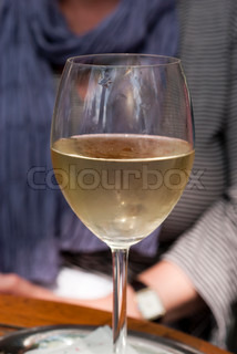 Glass of white wine close-up and outdoors on a restaurant in Bremen, Germany.