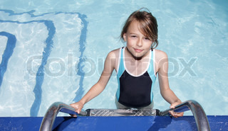 A ten year old blonde girl standing on the ladder to a swimmingpool