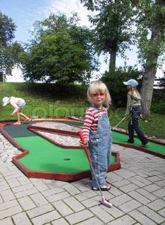 3 blonde Mädchen spielen Minigolf