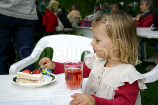 A little girl eating a strawberry cake decorated with the swedish flat. She is celebrating midsummer. She also has a glass of strawberry squash