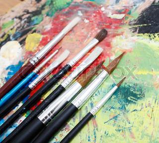 Rot, gelb, blau Gouache und Pinsel zum Zeichnen auf einem ...