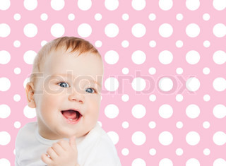 smiling baby girl face over pink polka dots