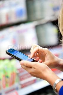 Nærbillede af en kvinde, med hendes mobil i hånaden