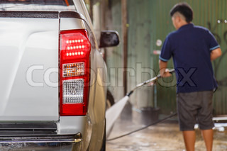 Blur of man using pressure washer for washing a car