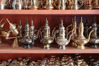 Eastern metal pitchers stand on a shelf in an Arab shop