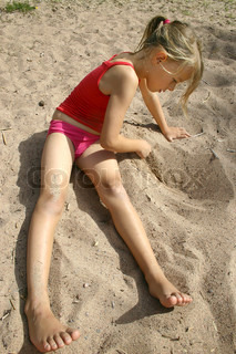 8 year old girl on the beach, writing in the sand. Vertical picture