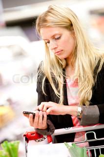 Kvinde kigger ned på hendes mobil, mens hun er ude og handle