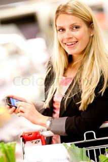 En kvinde kigger op fra hendes mobil mens hun handler