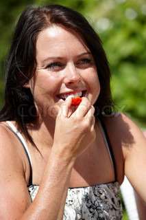 A young brunette eating tomato on a hot, summer day