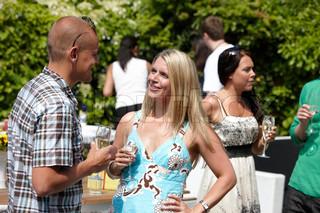 En lyshåret kvinde som snakker med en skaldet mand