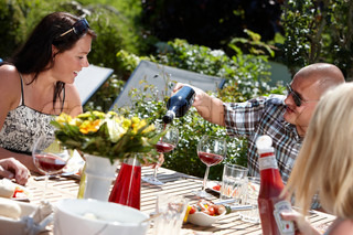 Happy young Europeans sharing wine during a summer lunch party (stock photo)