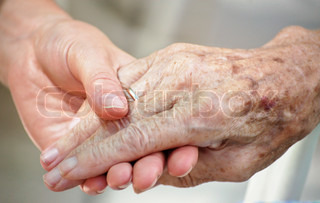 Elderly person's hand held by younger person's hand