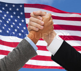 close up of hands armwrestling over american flag