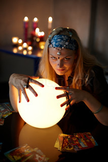 A female caucasian fortune teller with a glass ball