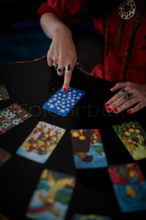 The hand of a fortune teller reading the tarot cards