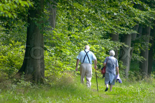 Two old persons / couple  in a forest path