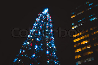 Night city with business centre and christmas tree