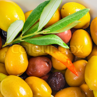 stuffed olives with an olive branch lie on a plate, closeup