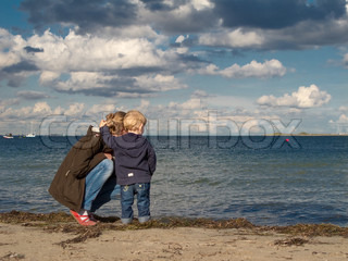 Mother and child at a beach looking towards the sea in autumn