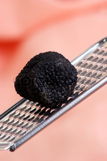 one organic summer truffle on a grater