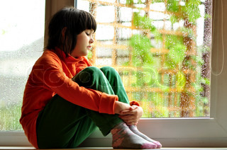 A child sitting on a windowsill and looking through the window on a rainy day