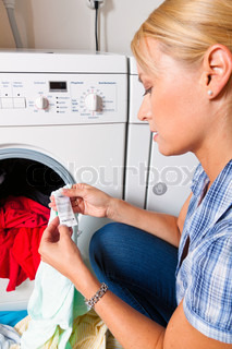 A young housewife with washing machine and clothes. Washing day.