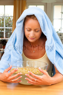 A young woman with colds and flu. Inhalation of herbs.