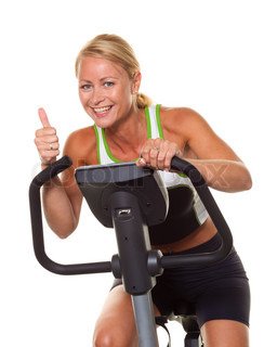 A young woman in training for endurance on exercise bike.